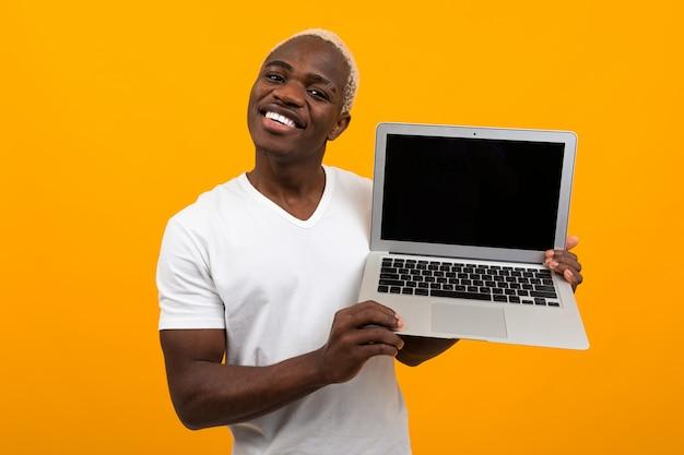 かなり笑顔でハンサムなアフリカ人が黄色の背景にモックアップでラップトップワイヤレスコンピューターを保持します