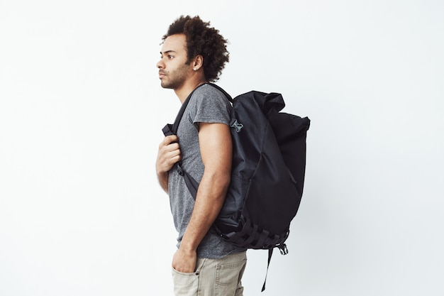 Handsome african man with rucksack standing in profile