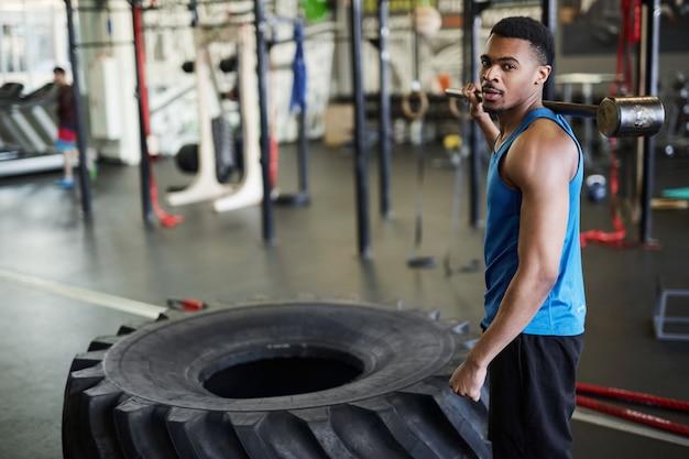Красивый африканский спортсмен позирует в тренажерном зале