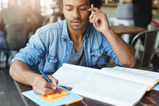 Handsome african student male in denim clothes sitting at university canteen with book and copybook writing some notes with pen communicating over smartphone with his friend having concentrated look