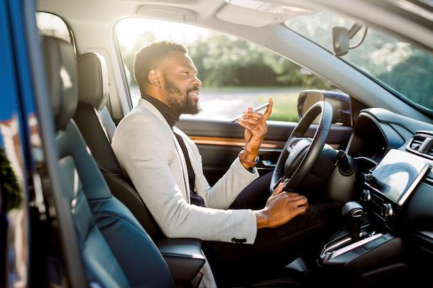 彼の手で携帯電話を保持している新しい高価な車に座っているハンサムなアフリカの青年実業家。車とビジネスのコンセプト