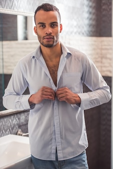 Handsome afro american businessman is buttoning shirt