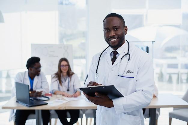 Красивый афро-американский врач в белом халате смотрит на камеру и улыбается
