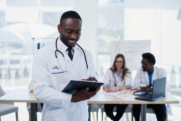 Handsome afro american doctor in white coat is looking at camera and smiling