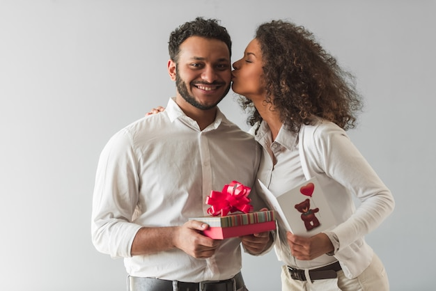 Handsome afro american guy is holding a gift box.