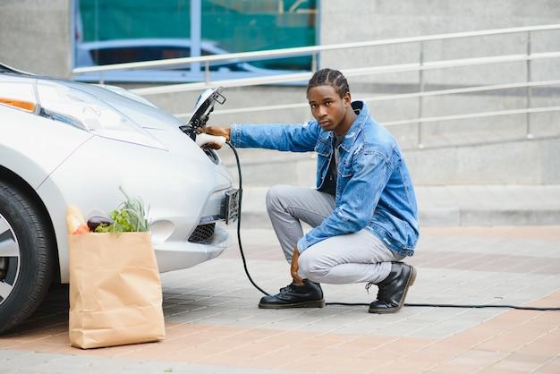 彼の新しい現代の電気自動車の近くに座って、充電器のプラグを保持しているハンサムなアフリカ系アメリカ人の男