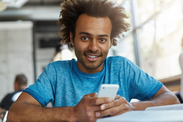 Handsome afro american guy with head of curly hair sitting in cozy cafeteria holding smart phone downloading music using free internet connection looking pleased and excited smiling