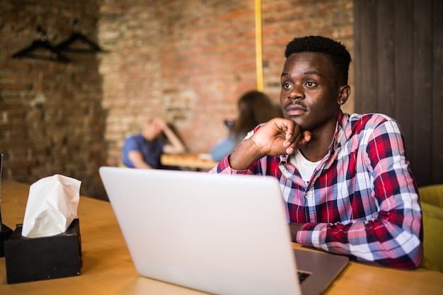 Handsome afro american man in casual clothes holding a cup of coffee and using laptop.