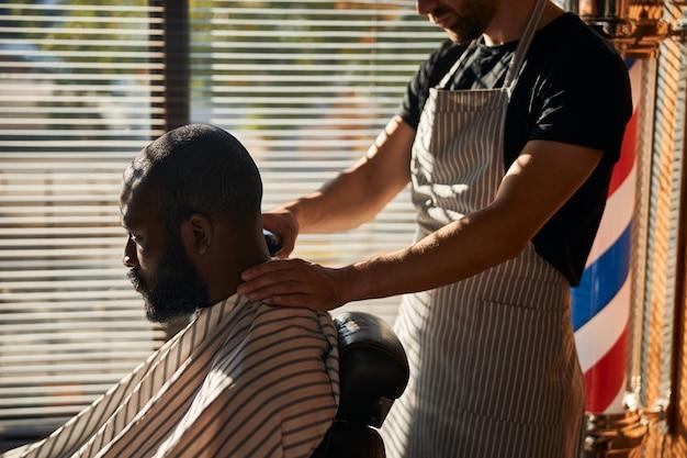 理髪店で散髪をしているハンサムなアフリカ系アメリカ人の男