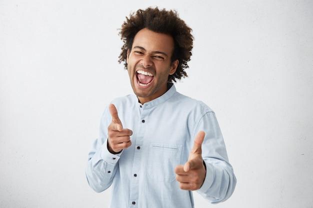 人差し指を指している幸福の完全な白いシャツでハンサムなアフロアメリカ人