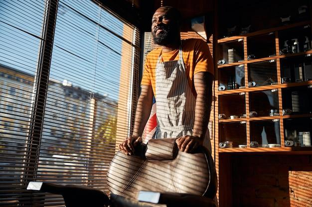 이발소 창가에 서 있는 잘생긴 아프리카계 미국인 남자