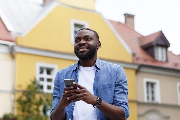 スマートフォンを使用して笑顔でハンサムなアフリカ系アメリカ人の男
