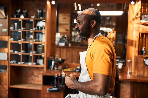 理髪店に立っているバリカンを持つハンサムなアフリカ系アメリカ人の男