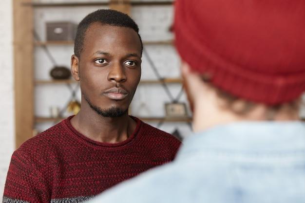 モダンなカフェのインテリアに立っているカジュアルなセーターを着ているハンサムなアフリカ系アメリカ人の若い男性