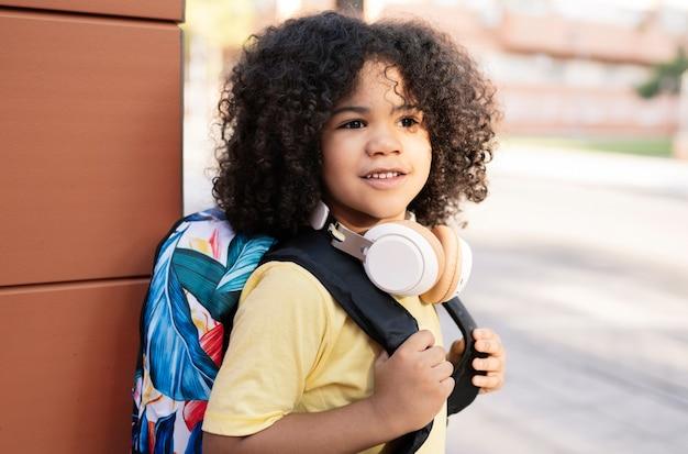 ハンサムなアフロ少年は学校のコンセプトにバックパックを運ぶ