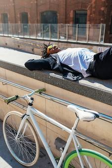 通りで彼の自転車の近くでリラックスしているハンサムなアフロ男。