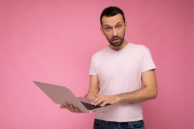 T- 셔츠에 카메라를보고 노트북 컴퓨터를 들고 잘 생긴 놀란 남자