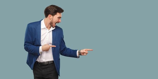 立って背景を指して、叫びながらコピースペースを見ている青いスーツを着たハンサムな驚いたひげを生やした男。スタジオ、青い背景で隔離の屋内ショット。