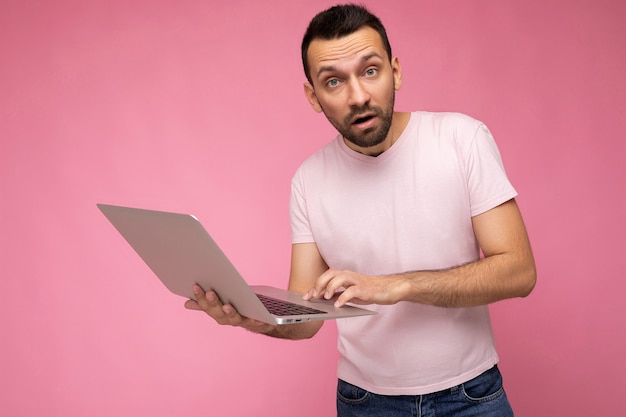 Handsome amazed and surprised man holding laptop computer