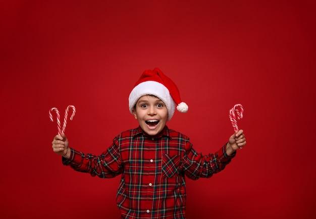 Красивый удивительный мальчик, красивый ребенок позирует на цветном красном фоне с рождественскими леденцами, сладкими полосатыми леденцами в руках, мило улыбается, глядя в камеру. новогодняя концепция с копией пространства