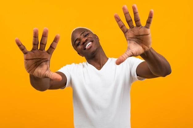 白いtシャツでハンサムなアメリカ人の男は分離された黄色の彼の手を差し出します