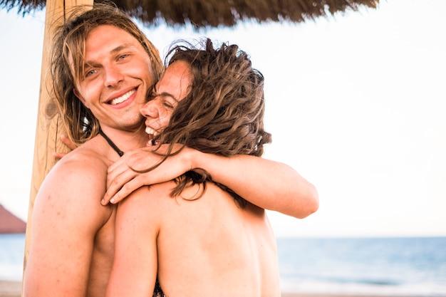 Красивый и привлекательный молодой мужчина и женщина обнимаются и наслаждаются отношениями во время летних каникул на пляже