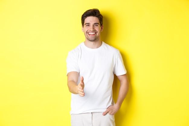 잘 생기고 자신감 있는 남자가 악수를 하기 위해 손을 내밀고, 인사하고, 인사하고, 노란색 배경 위에 흰색 티셔츠를 입고 서 있습니다.