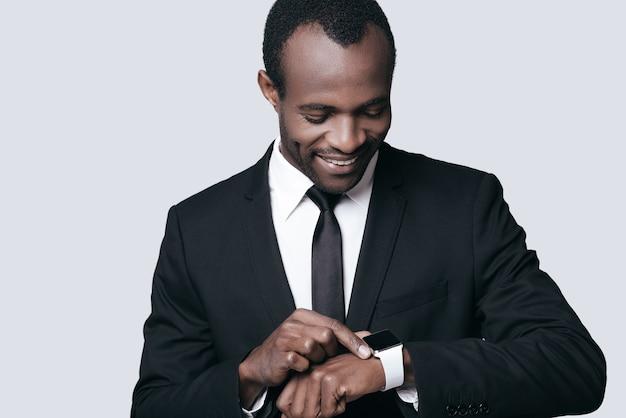 잘생기고 자신감이 넘칩니다. 회색 배경에 서서 시계를 보고 웃고 있는 젊은 아프리카 남자