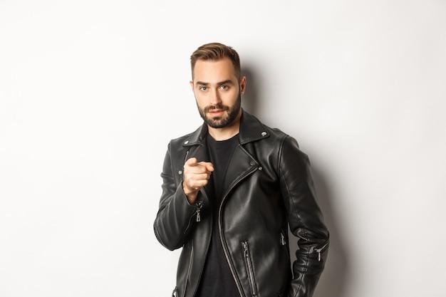 カメラに指を指し、革のジャケットを着て、生意気に立っているハンサムでクールなひげを生やした男