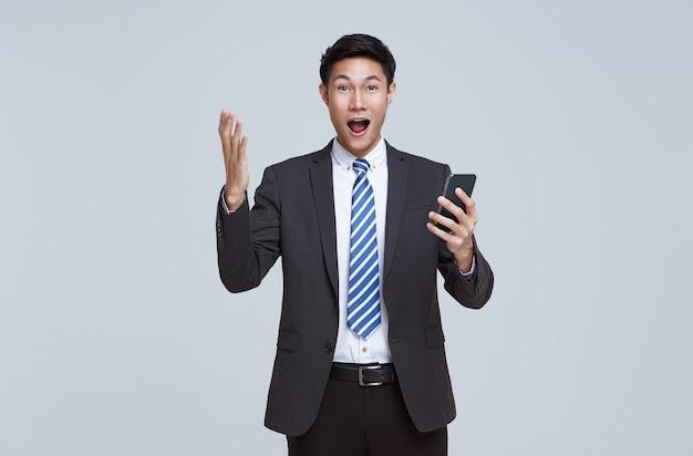 スマートフォンを使用して彼のフォーマルなスーツに興奮しているハンサムでフレンドリーな顔のアジアのビジネスマン