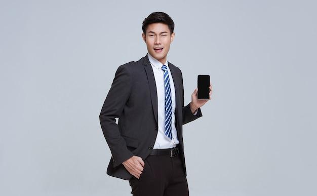 ハンサムでフレンドリーな顔のアジア人ビジネスマンがフォーマルなスーツを着て笑顔