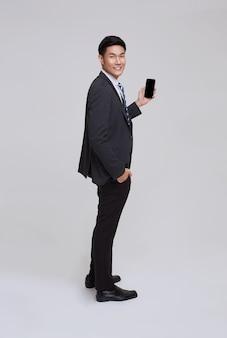ハンサムでフレンドリーな顔のアジアのビジネスマンは、白い背景のスタジオショットでスマートフォンを使用してフォーマルなスーツで笑顔。