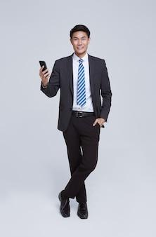 ハンサムでフレンドリーな顔のアジアのビジネスマンは、白い背景のスタジオショットでスマートフォンを使用してフォーマルなスーツで微笑んでいます。