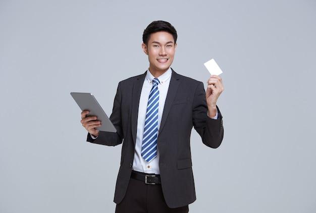 ハンサムでフレンドリーな顔のアジアのビジネスマンは、白い背景のスタジオショットでタブレットとクレジットカードを使用して彼のフォーマルなスーツで笑顔。