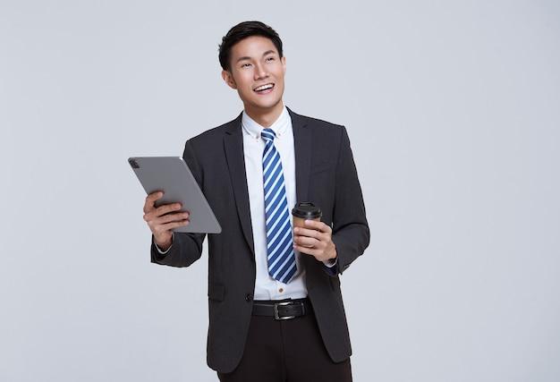 ハンサムでフレンドリーな顔のアジアのビジネスマンは、白い背景のスタジオショットでタブレットを使用してフォーマルなスーツで微笑んでいます。
