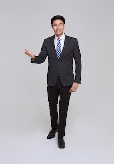 ハンサムでフレンドリーな顔のアジアのビジネスマンは、白い背景のスタジオショットでフォーマルなスーツに笑顔。