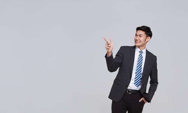 フォーマルなスーツを着たハンサムでフレンドリーな顔のアジア人ビジネスマンの笑顔は、白い背景のスタジオショットのスペースをコピーするために提示された彼の手を指します。