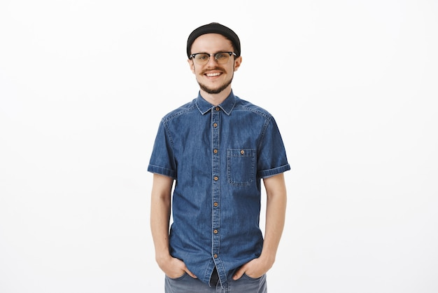 Красивый и забавный стильный европейский парень в черной шапочке и очках с бородой, держась за руки в карманах, радостно улыбается, чувствуя удовлетворение после того, как все планы выполнены, беззаботно позирует над серой стеной