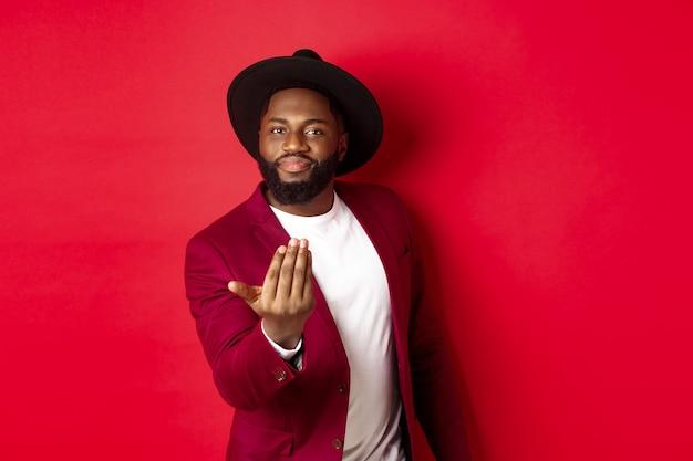 ハンサムで男性的な黒人男性が近づいてきて、前に進むように誘い、あなたを呼び、赤い背景の上に立っています