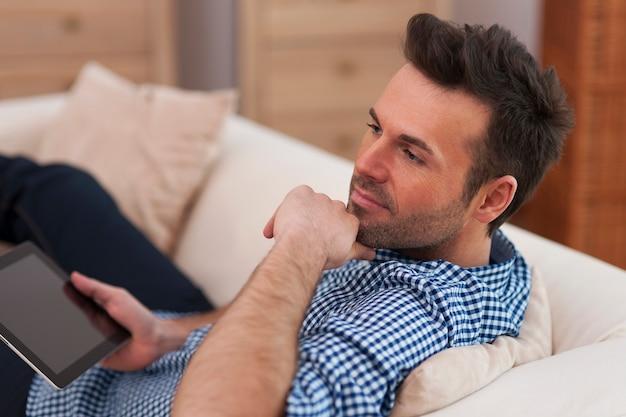 デジタルタブレットでハンサムで物思いにふける男