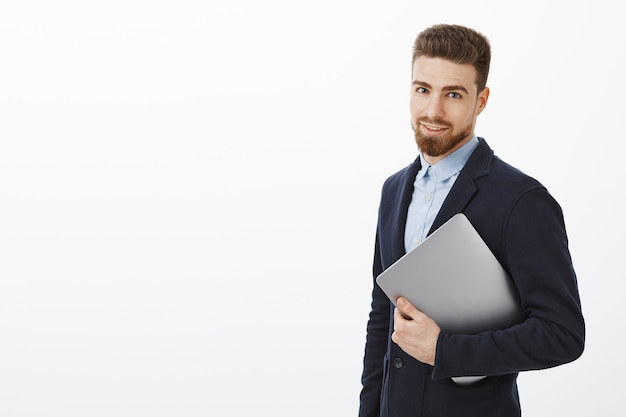 ハンサムでスタイリッシュなビジネスマンは、ビジネスの仕組みを知っています。ラップトップコンピューターを手に持って、灰色の壁に自信を持って見つめるスーツを着た、成功し、断固とした見栄えの良い男