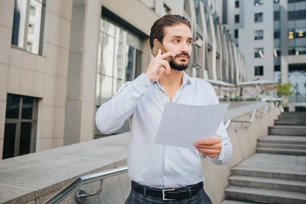 Красивый и стильный бизнесмен стоит и позирует. он говорит по телефону и смотрит направо. парень держит лист бумаги в левой руке. молодой человек стоит на ступеньках.