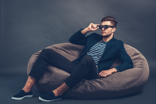 Красиво и стильно. уверенный молодой красавец поправляет свои солнцезащитные очки и смотрит в сторону, сидя на мешке с фасолью на сером фоне