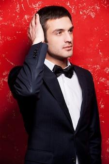 ハンサムでスタイリッシュ。スーツと蝶ネクタイのハンサムな若い男は彼の髪に触れて、赤い背景に立っている間目をそらします