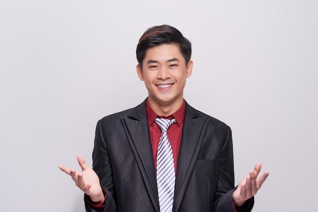 カメラに向かって微笑んで白い背景に立って、スーツ、ネクタイ、ベストを着たハンサムで身なりのよいビジネスマン。