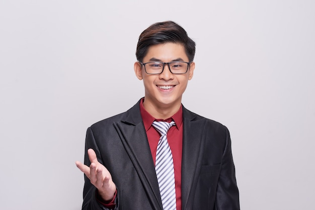 양복, 넥타이, 조끼를 입고 카메라를 향해 웃고 있는 흰색 배경에 서 있는 잘생기고 잘 차려입은 사업가.