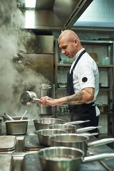 Красивый и молодой шеф-повар готовит домашнюю итальянскую пасту на кухне ресторана