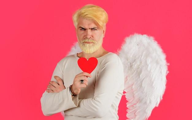 バレンタインの心を持つハンサムな天使。白い翼を持つキューピッドの男。愛の概念。