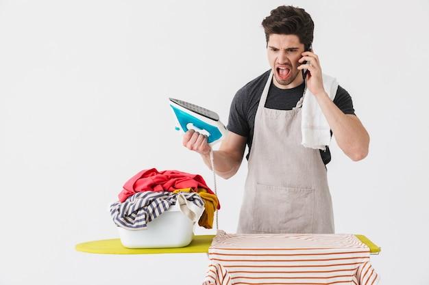 Красивый сердитый домработник брюнетки в фартуке, стоящий изолированно над белой, гладит одежду на доске, разговаривает по мобильному телефону