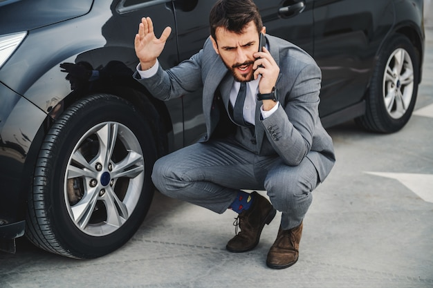Handsome angry caucasian bearded businessman crouching next to his car and calling service.